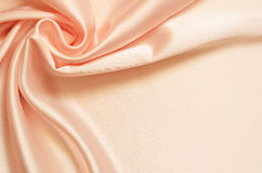 Background with satin drapery. Peach background with satin drapery in the corner Stock Image