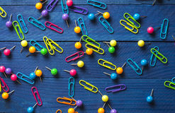 Background of scattered colored round pins and paper clips on a table Royalty Free Stock Photos