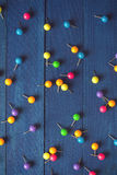 Background of scattered colored round pins on wooden boards Stock Photography