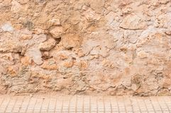Old rustic stone wall background scene with pavement. Background scene of vintage wall with sidewalk and copy space stock photo