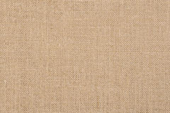 A background of a scratchy burlack material in an even light brown color. Stock Photos