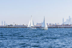 background seascape two sailboat met opposite the Dubai Marina Royalty Free Stock Image