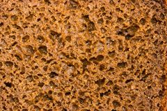 Background of cut of brown rye and wheat bread. Background of section of brown rye and wheat bread loaf with added rye malt and coriander closeup stock photos