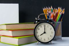 Background of sets of office items and a black alarm clock on colorful books, next to a glass with pencils, there is a place for. An inscription royalty free stock images