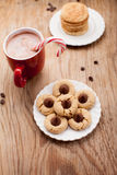 Background setting of holiday cookies and hot chocolate. Plate of snickerdoodle cookies, hot chocolate, peppermint candy cane, and chocolate peanut blossom Stock Image