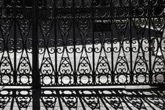Background of shadow of wrought iron bars. Door with  wrought iron bars and shadows on the pavement Stock Photos