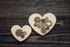 Background with shape of hearts, the gear mechanism and a key on Stock Images