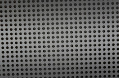 Background sheet of metal covered with lines of circular holes. Royalty Free Stock Photography