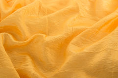 Background of a shining rippled golden satin. Gold satin or silk fabric background Royalty Free Stock Photo