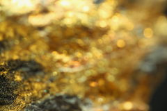 Background with shiny yellow gold ore. Microscope image Stock Images