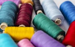 Background shot of bright thread spools on white fabric - image royalty free stock photos