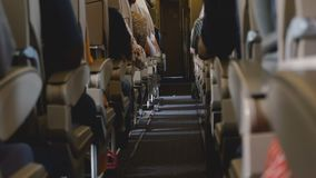 Background shot of modern airplane economy class interior clear aisle during flight with passengers in their seats. Concept of modern travel and transportation stock video footage