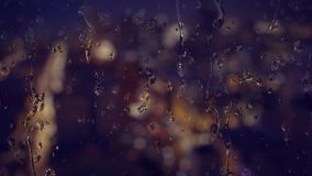 Water Dripping on Glass in Night City Background. 8481 Background shot of rainy water drips on a window glass.  A nighttime city scene with traffic is defocused stock footage