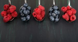 Background of six metal spoons with raspberries and blueberries on a black background. Background of six metal  spoons with raspberries and blueberries on a Stock Image