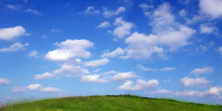 Background Of Sky And Clouds above the hill. Background Of Sky And Grass - wide view Royalty Free Stock Photos