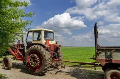 Background of sky, clouds, field  and wheeled tractor Stock Photo