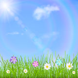 Background with sky, sun, clouds, rainbow, grass and flowers. Natural background with blue sky, sun, clouds, rainbow, green grass and multicolored flowers Stock Image