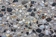 Background of small pebbles in a concrete wall stock image
