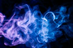 Background from the smoke of vape. Colorful blue smoke on a black isolated background. Background from the smoke of vape stock image