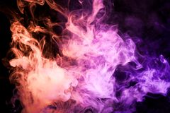 Background from the smoke of vape. Colorful red and  pink a smoke  on a black isolated background. Background from the smoke of vape Royalty Free Stock Photography