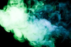 Background from the smoke of vape. Colorful yellow  and green a smoke  on a black isolated background. Background from the smoke of vape Royalty Free Stock Photo
