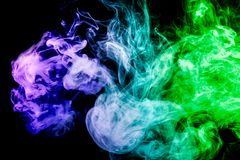 Background from the smoke of vape. Dense multicolored smoke of blue and green colors on a black isolated background. Background of smoke vape royalty free stock photography