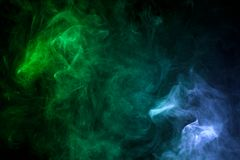 Background from the smoke of vape. Dense multicolored smoke of  green and blue colors on a black isolated background. Background of smoke vape Royalty Free Stock Image