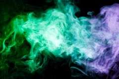 Background from the smoke of vape. Dense multicolored smoke of  green and blue colors on a black isolated background. Background of smoke vape Stock Photography