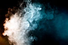 Background from the smoke of vape. Dense multicolored smoke of   red, blue on a black isolated background. Background of smoke vape Royalty Free Stock Photo