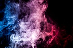 Background from the smoke of vape. Dense multicolored smoke of   red, blue and pink colors on a black isolated background. Background of smoke vape Stock Image