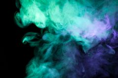 Background from the smoke of vape. Thick colorful smoke of green, blue on a black isolated background. Background from the smoke of vape Stock Image