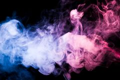 Background from the smoke of vape. Thick colorful smoke of pink, blue on a black isolated background. Background from the smoke of vape Royalty Free Stock Photo