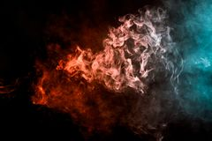 Background from the smoke of vape. Thick colorful smoke of red and blue on a black isolated background. Background from the smoke of vape Stock Photography