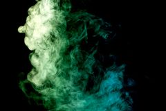 Background from the smoke of wipe. Dense multicolored smoke of   green and blue colors on a black isolated background. Background of smoke vape Stock Photography