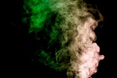 Background from the smoke of wipe. Dense multicolored smoke of   green and blue colors on a black isolated background. Background of smoke vape Royalty Free Stock Images