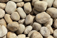 Background of smooth stones. Background of smooth light brown stones or pebbles in heap Stock Image