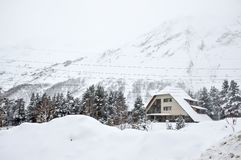 House in the winter forest on the background of snowy mountains royalty free stock photo