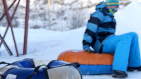 Background snow tubing blurry. Child aduld snow tubing sunny day stock video footage