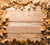 Frame of autumn leaves on wooden boards royalty free stock photography