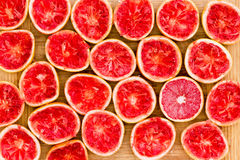 Background of squeezed ruby grapefruit halves. Background pattern of fresh squeezed ruby grapefruit halves arranged side by side on a bamboo cutting board viewed royalty free stock photography