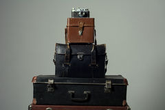 Background stack of old shabby suitcase with a camera in bag. Stock Photo