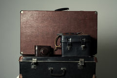 Background stack of old shabby suitcases and the camera Stock Photography