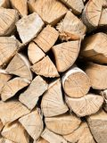 Background of stacked split logs closeup. Wood in the woodpile royalty free stock image