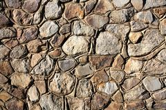 Background - Stacked Stone Wall. Background - a wall made of natural stone of different sizes in a sunny day Stock Photo