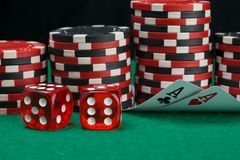 On the background of stacks of chips to play in the casino, two folded cards to view the denomination on the green table, next to. The two red cubes royalty free stock photo