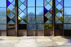 Background with stained glass wall in a room and hydraulic pavement floor with some reflections. Royalty Free Stock Images