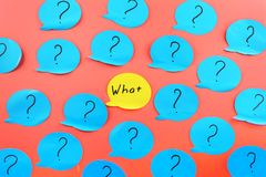 Background with stickers. The phrase, WHAT is in the center, on the yellow sticker, among the question marks on the blue. Unusual background with stickers. The royalty free stock images