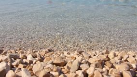 Stone beach and transparent water. Background stone beach and transparent water, Croatia, Sumartin stock video