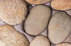 Background stone smooth pebbles light beige part wall close-up base geology substrate eco Royalty Free Stock Photography