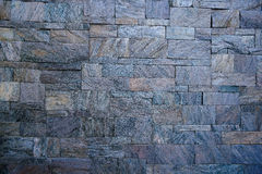 Background stone wall. The external wall is paved with stone stock photos